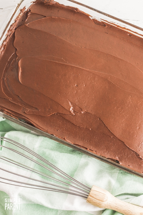 Frosted chocolate cake in glass baking dish