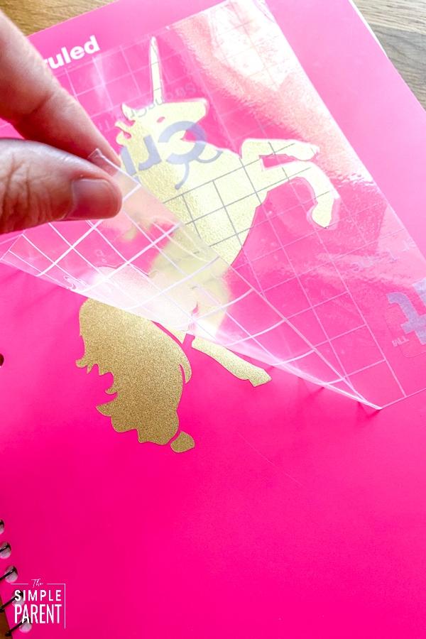 Peeling transfer tape of vinyl unicorn design on front of notebook