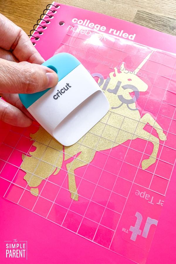 Placing vinyl unicorn design on pink notebook