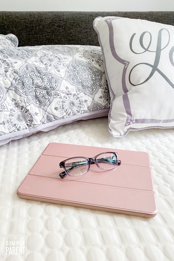 Tablet and glasses laying on bed
