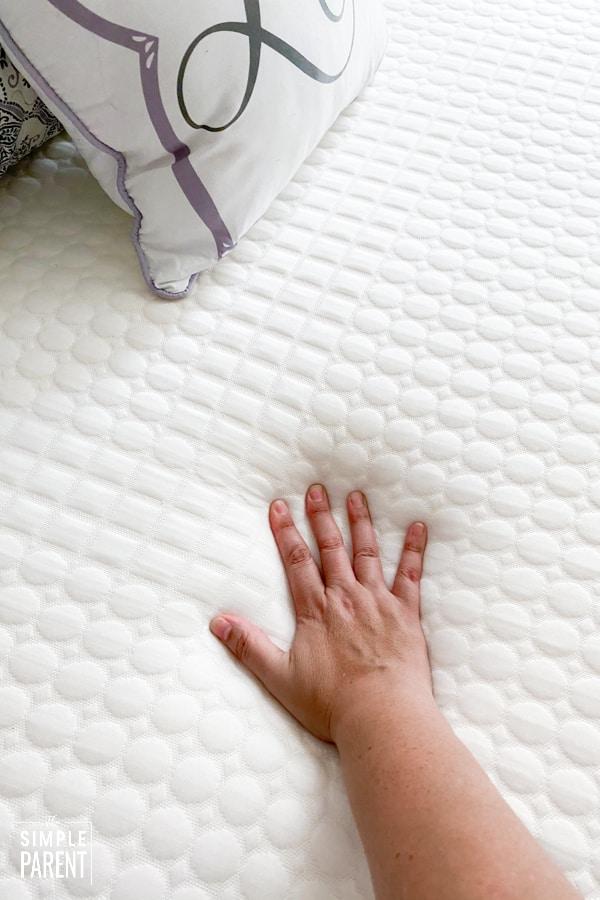 Hand pressing down on foam Spoon Mattress
