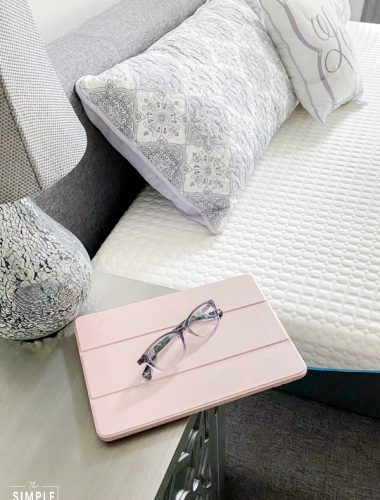 Tablet and glasses sitting on a nightstand near the bed
