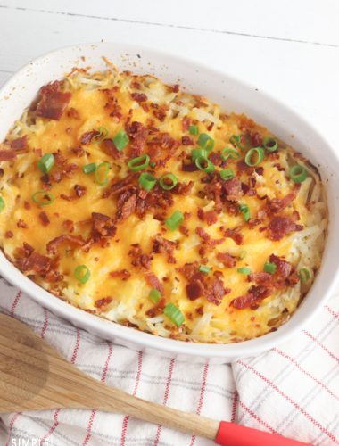 Loaded Hashbrown Casserole in white baking dish with wooden spoon