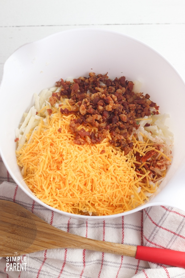 Cheese, bacon, and hashbrowns in a mixing bowl