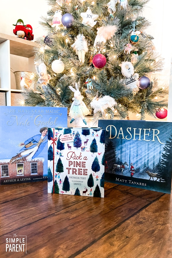 Holiday books for kids in front of Christmas tree