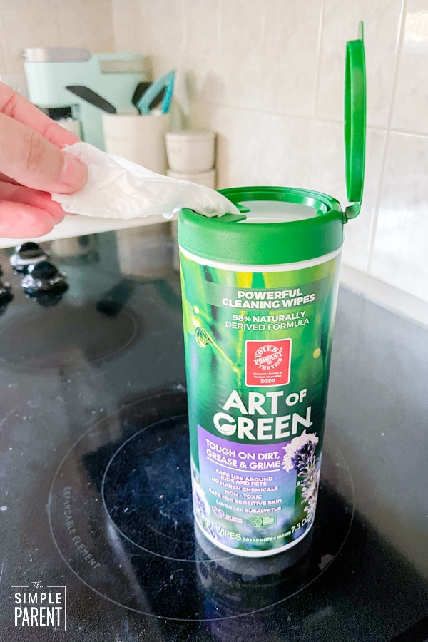 Pulling a cleaning wipe out of a container of Art of Green wipes