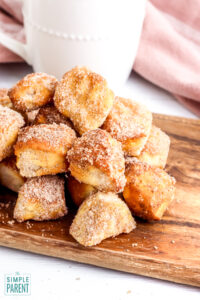 Stack of air fryer donut bites with cinnamon sugar on a cutting board