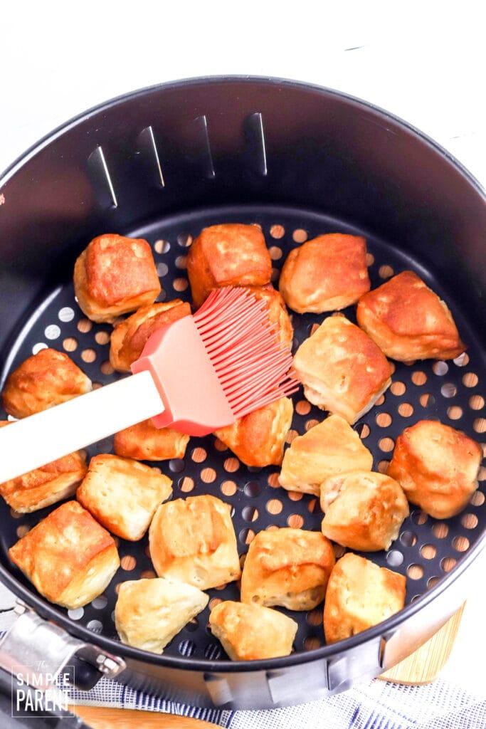 Brushing butter on air fryer donut holes