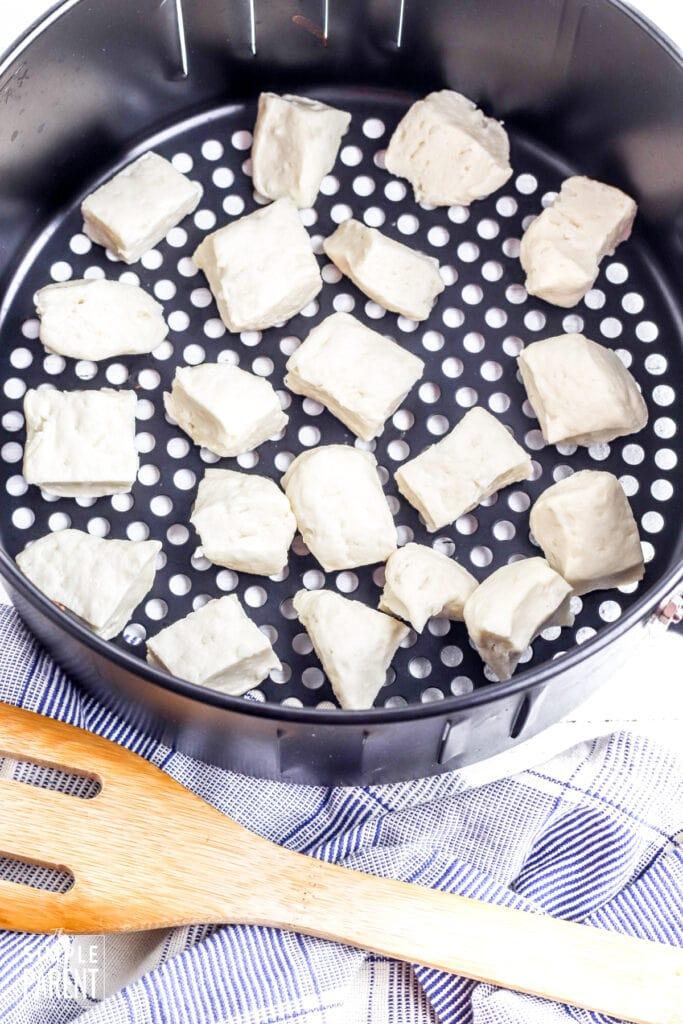 Biscuit dough pieces in air fryer basket