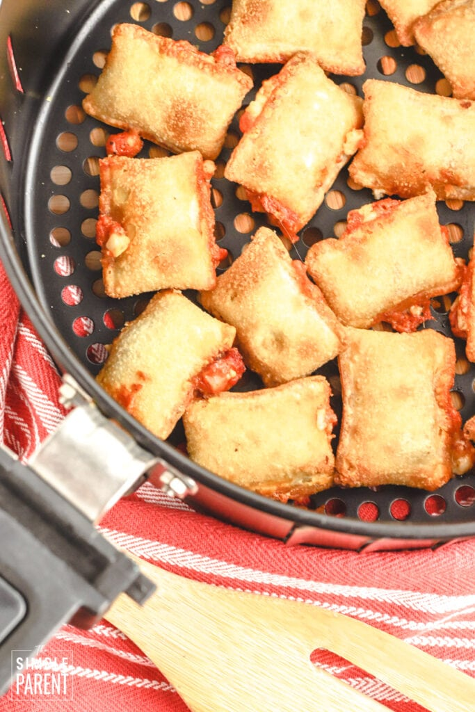Cooked pizza rolls in basket of air fryer