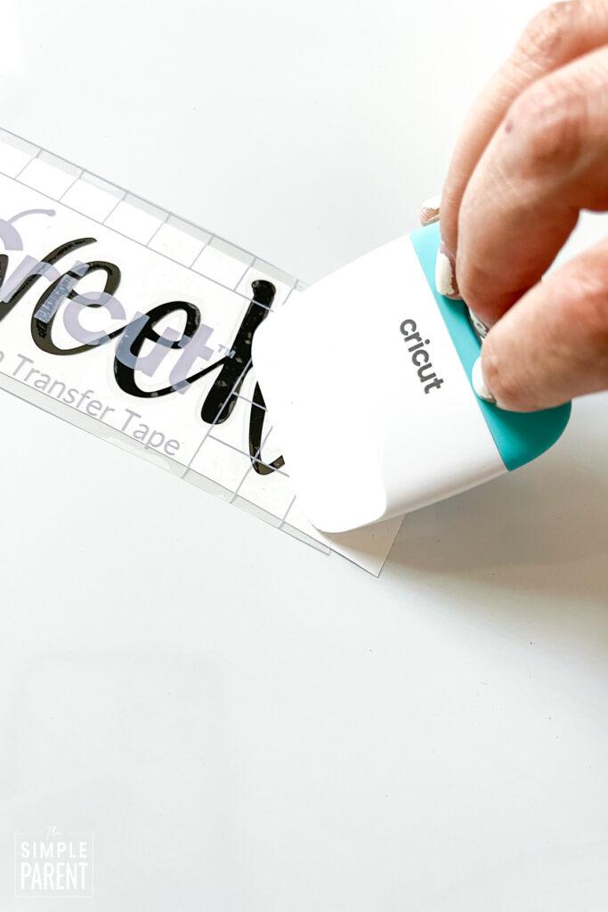 Using Cricut scraper to smooth transfer tape over black vinyl letters