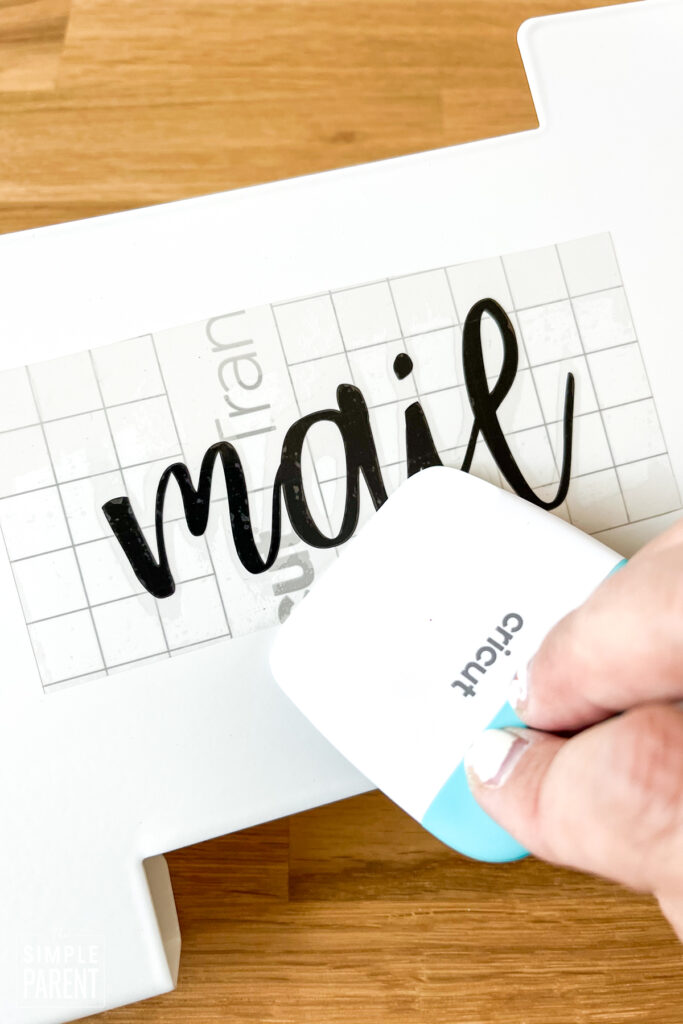 Smoothing vinyl letters onto mail holder
