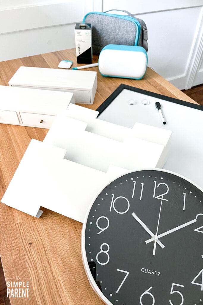Clock, dry erase board, file folder holders, and Cricut Joy on counter top