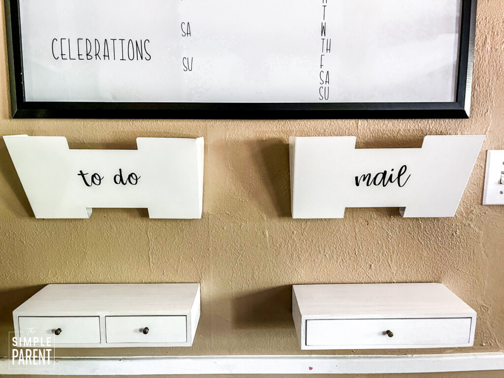 Customized mal boxes and small shelves hung on the wall under a calendar