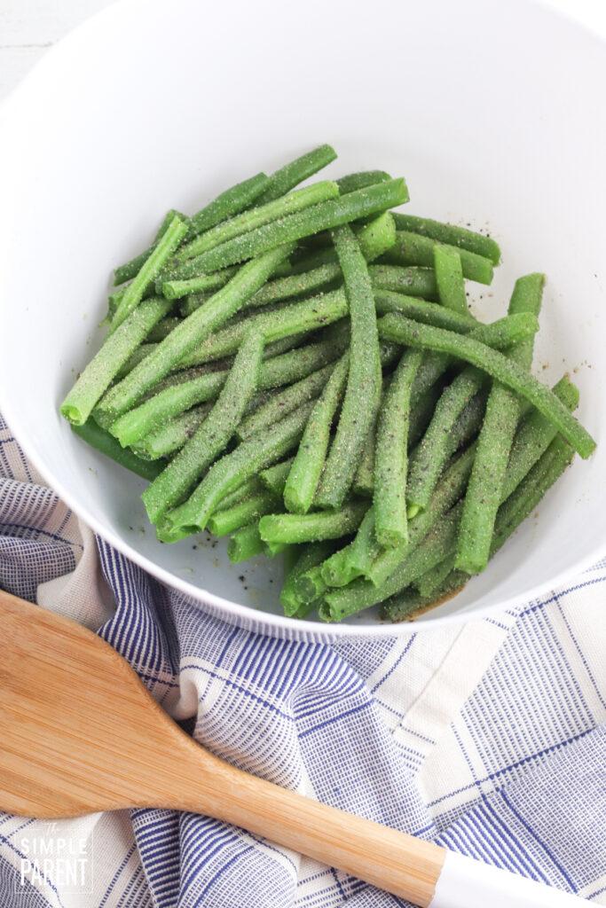 Fresh green beans in white mixing bowl