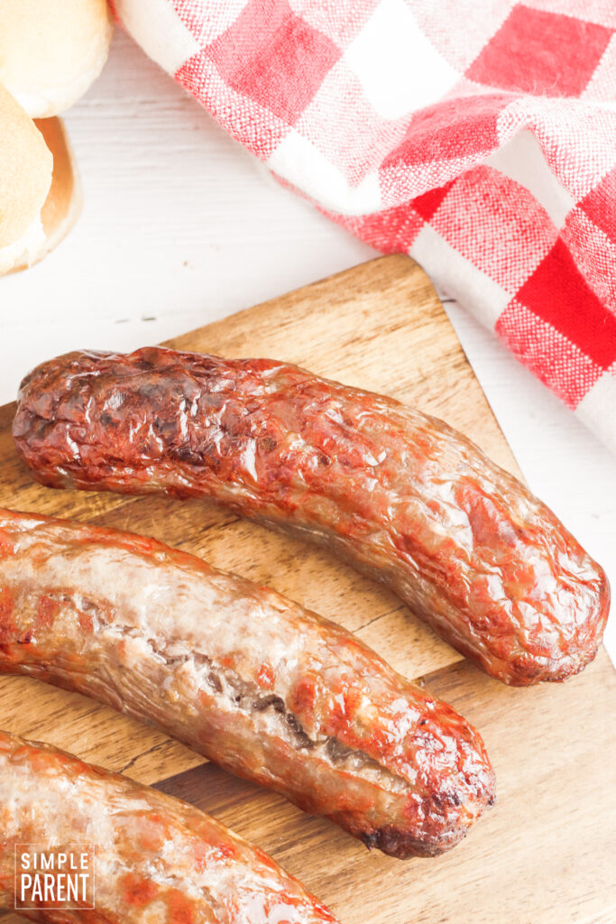 Cooked brats on cutting board