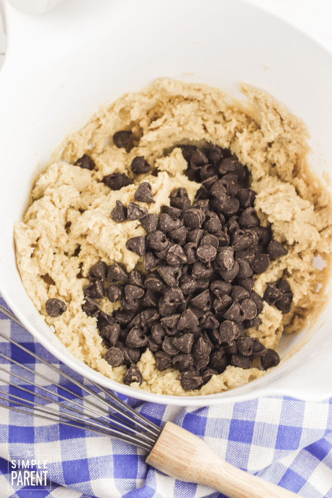 Chocolate chips in cookie dough in white mixing bowl
