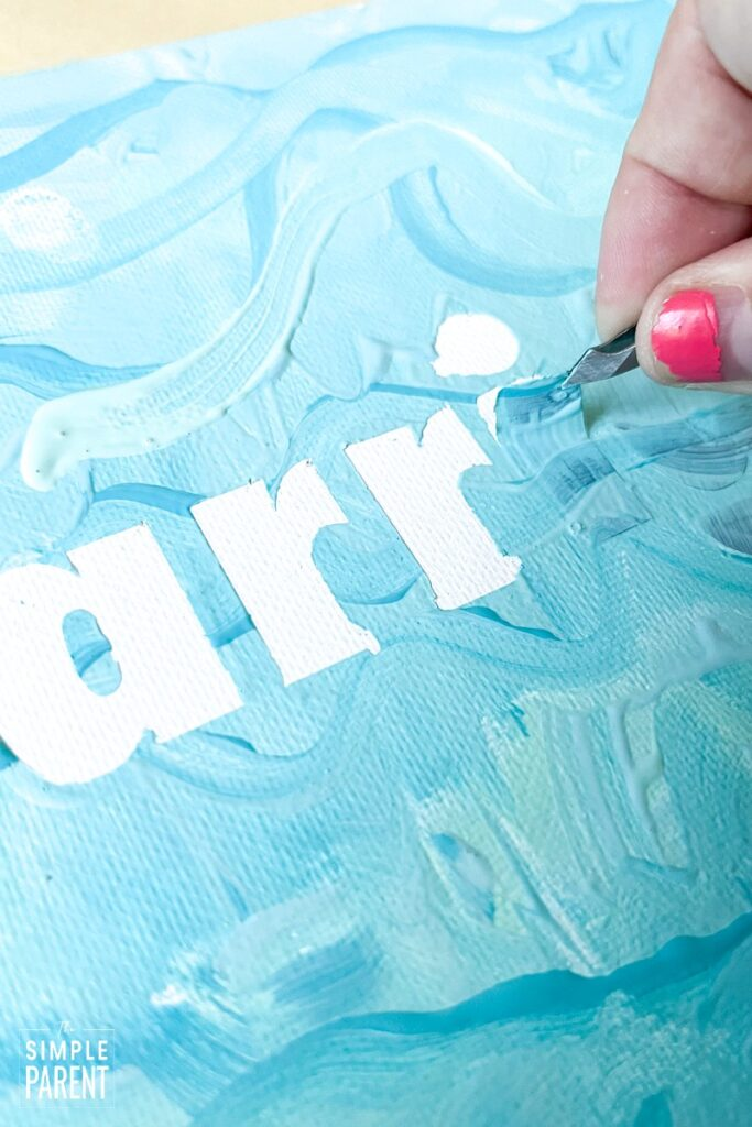 Using tweezers to remove vinyl letters from painted canvas