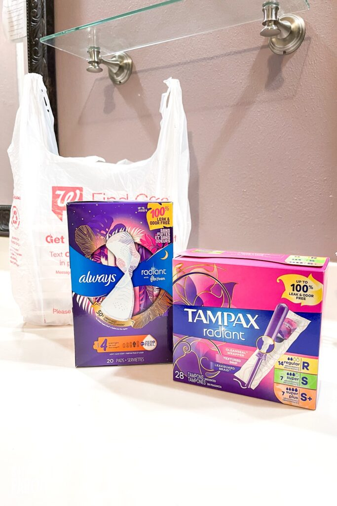 Tampax and Always packages in front of Walgreens bag on bathroom counter